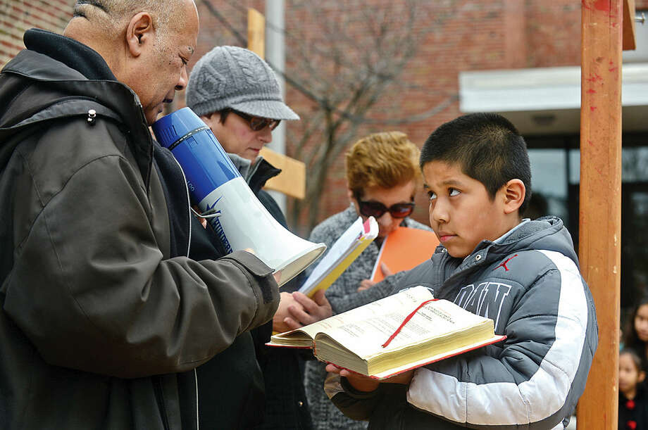 Hour photo / Erik Trautmann Christian Hernandez, 8, helps Father Frantz Desruisseaux read prayer as nearly 100 parishioners of St. Joseph Church observe the Living Stations of the Cross at the church in South Norwalk on Good Friday.