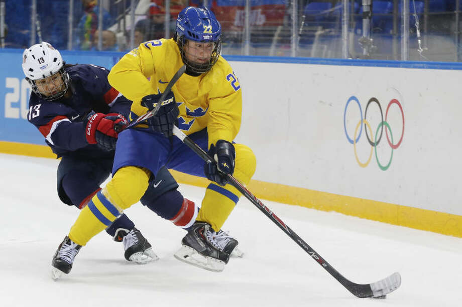 Emma Eliasson of Sweden takes control of the puck away from Julie Chu of the United States during the first period of the 2014 Winter Olympics women's semifinal ice hockey game at Shayba Arena Monday, Feb. 17, 2014, in Sochi, Russia. (AP Photo/Petr David Josek)