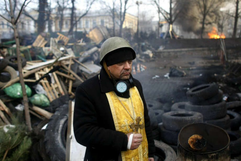 A priest stands on the barricades at Independence Square in Kiev, Ukraine, Friday, Feb. 21, 2014. Ukraine's presidency said Friday that it has negotiated a deal intended to end battles between police and protesters that have killed scores and injured hundreds, but European mediators involved in the talks wouldn't confirm a breakthrough. (AP Photo/ Marko Drobnjakovic)