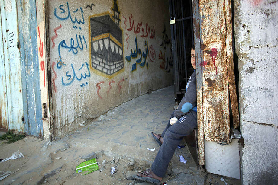 A Palestinian boy sits next to an old wall mural depicting the Kaaba, Islam's holiest site and a center point of the annual Hajj pilgrimage, in the Rafah refugee camp, southern Gaza Strip, Friday, Feb. 27, 2015. With the war-battered Gaza Strip's borders closed, thousands of people have been shut out of a Muslim pilgrimage to Saudi Arabia because they cannot leave the sealed territory. Some 7,500 Gazans have sought to travel to Mecca, Saudi Arabia, for the minor umrah pilgrimage but have been turned away because Egypt restricts movement in and out of the coastal enclave.(AP Photo/Khalil Hamra)
