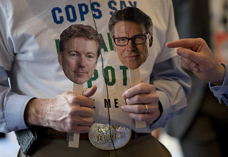 """Howard """"Cowboy"""" Woodward holds images Sen. Rand Paul, R-Ky., left, and former Texas Gov. Rick Perry as he is interviewed during the Conservative Political Action Conference (CPAC) in National Harbor, Md., Thursday, Feb. 26, 2015. (AP Photo/Carolyn Kaster)"""