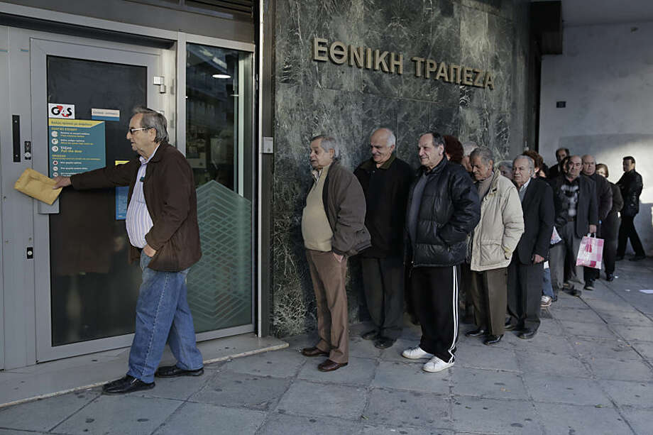 Pensioners wait to enter a National Bank branch to receive their pensions, which were deposited in the bank, on Thursday, Feb. 26, 2015. This is a monthly scene in Greece, where retirees have seen their pensions cut and have frequently run out of money by the time the next monthly installment is paid. Greece's prime minister Alexis Tsipras held a marathon meeting with his party's lawmakers Wednesday, briefing them on pledges made to European creditors to win a four-month extension of the country's bailout amid simmering party discontent over what some see as a capitulation. The meeting, which was held behind closed doors, lasted more than 11 hours. (AP Photo/Petros Giannakouris)