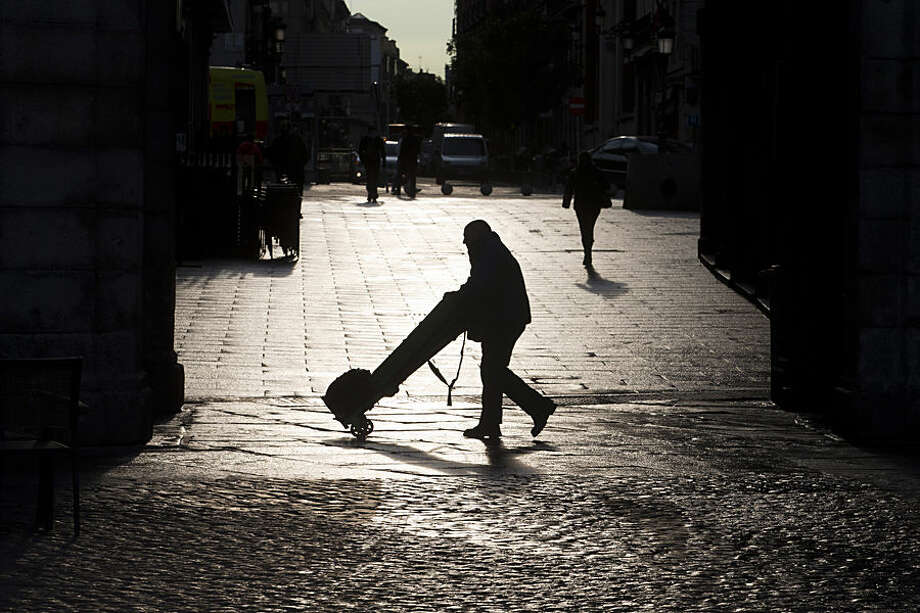 A man pushes a barrow in Madrid, Spain, Thursday, Feb. 26, 2015 as the day gets underway in the Spanish capital. (AP Photo/Paul White)