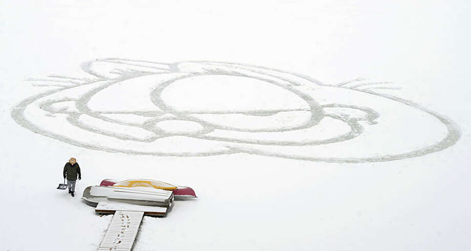 Les Kroemer is dwarfed by a likeness of Jim Davis' comic strip character Garfield, Thursday, Feb. 26, 2015, in Marion, Ind. Kroemer shoveled the likeness onto the frozen surface of Wagner Lake behind his home. (AP Photo/The Chronicle-Tribune, Jeff Morehead)