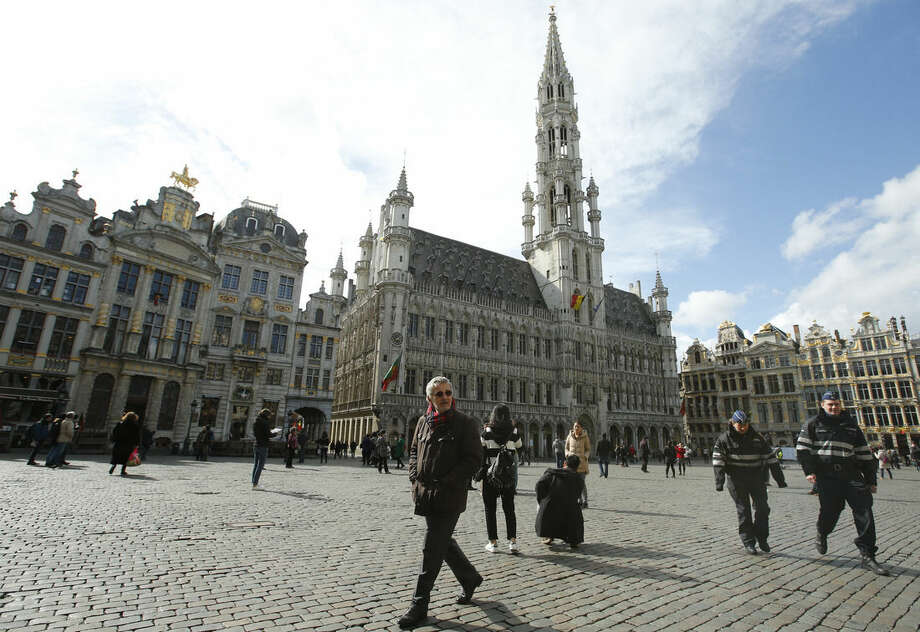 Police patrol through the Grand Place, as tourists wander in Brussels, Monday, March, 28, 2016. The Belgian health minister says four of those wounded in the suicide bombings last week have died in the hospital, bringing the number of victims of the bombings to 35.(AP Photo/Alastair Grant)