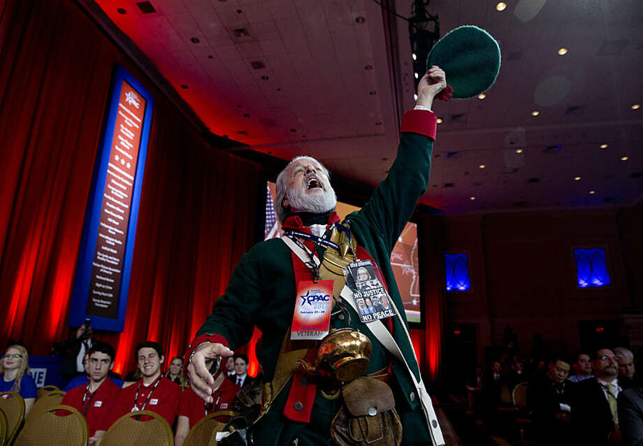 Golden Isles Tea Party activist William Temple, from Brunswick, Ga., dressed as Button Gwinnett, cheers as Ben Carson speaks during the Conservative Political Action Conference (CPAC) in National Harbor, Md., Thursday, Feb. 26, 2015. Button Gwinnett, of Georgia, was a signer of the Declaration of Independence. (AP Photo/Carolyn Kaster)