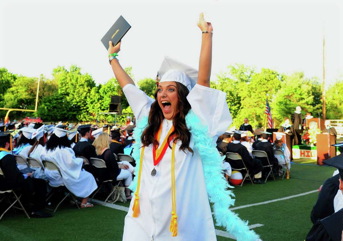 Graduate Madison Zayas holds her diploma high to show her family during Shelton High School's Class of 2016 Commencement Exercises in Shelton, Conn., on Friday June 10, 2016.