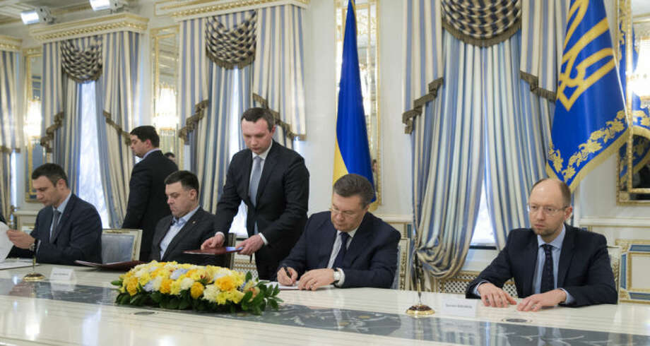 Ukrainian President Viktor Yanukovych, second right, and Ukrainian opposition leaders, Arseniy Yatsenyuk, right, Vitali Klitschko, left, Oleg Tjagnibok, second left, attend a signing ceremony of the agreement in Kiev, Ukraine, Friday, Feb. 21, 2014. Ukraine's opposition leaders signed a deal Friday with the president and European mediators for early elections and a new government in hopes of ending a deadly political crisis. Russian officials immediately criticized the deal and protesters angry over police violence showed no sign of abandoning their camp in central Kiev. (AP Photo/Andrei Mosienko, Presidential Press Service, Pool)
