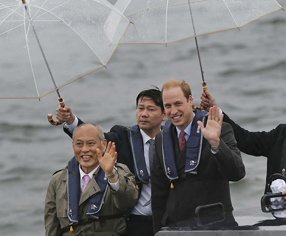 Britain's Prince William, right, waves with Tokyo Gov. Yoichi Masuzoe from a boat in Tokyo harbor after arriving in Tokyo Thursday, Feb. 26, 2015. William is on a four-day visit to Japan. (AP Photo/Koji Sasahara)