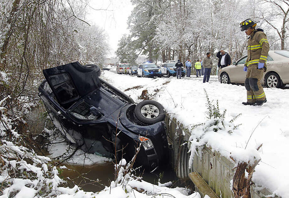 Raleigh emergency personnel respond to an accident involving a vehicle that slid on an icy road and overturned in a ditch, Thursday, Feb. 26, 2015, in Raleigh, N.C. All across the Carolinas, people were digging out of a wintry mix of snow and ice that created treacherous roads and left thousands of people without power. (AP Photo/The News & Observer, Chris Seward)
