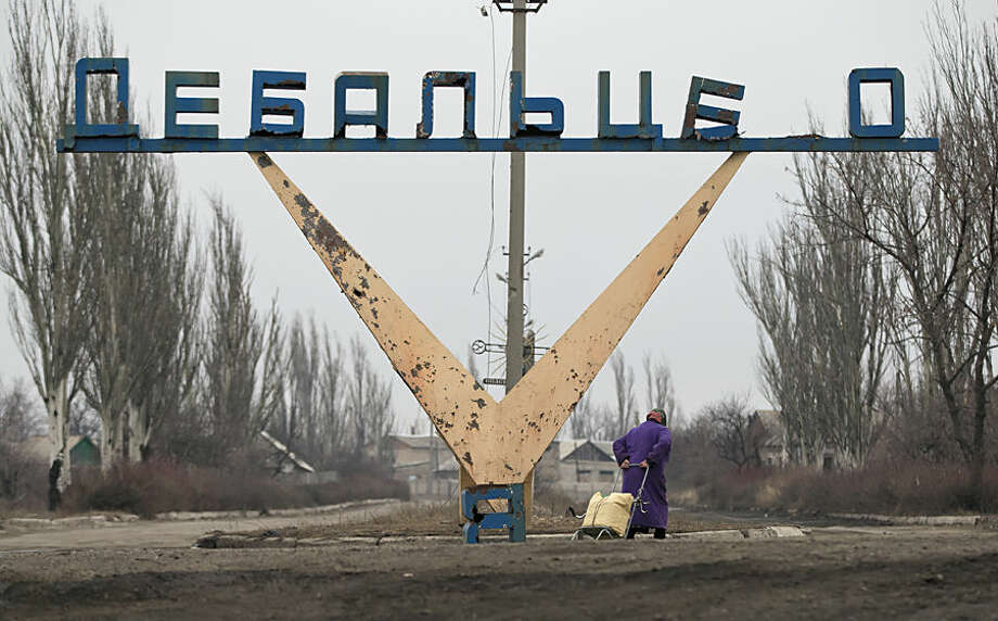 An elderly woman drags a cart with her belongings on the outskirts of Debaltseve, Ukraine, Thursday, Feb. 26, 2015. After weeks of relentless fighting, which inflicted severe damage to most buildings the embattled Ukrainian rail hub of Debaltseve fell last week to Russia-backed separatists. (AP Photo / Vadim Ghirda)