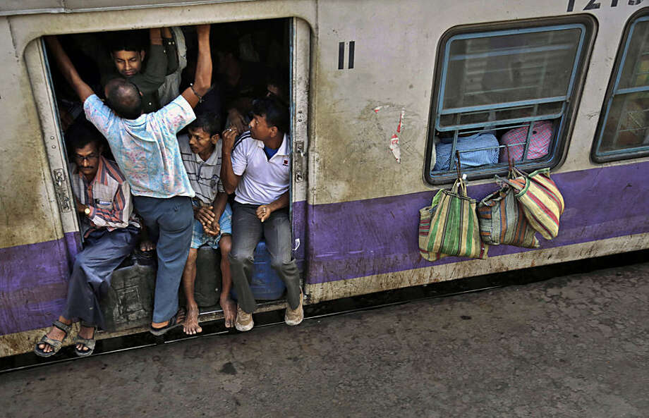 Indian passengers crowd the doorway of one of the coaches of a suburban train as it prepares to leave a station on the outskirts of Kolkata, India, Thursday, Feb. 26, 2015. Indian Railway minister Suresh Prabhu Thursday unveiled the budget for one of the world's largest railways systems that serves more than 23 million passengers a day. (AP Photo/Bikas Das)