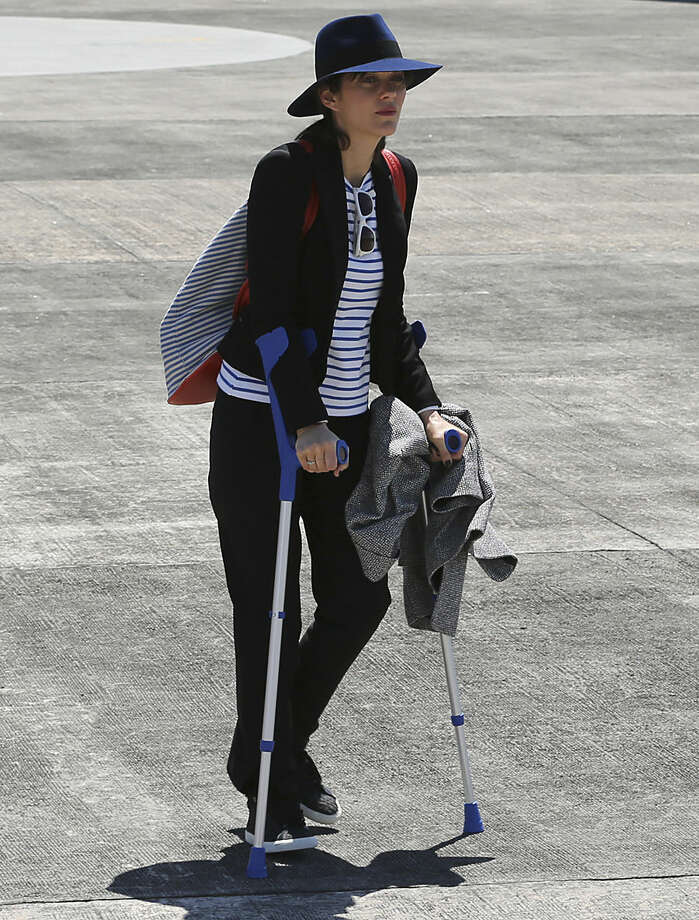 French award-winning actress Marion Cotillard walks with crutches as she arrives with French President Francois Hollande at the Villamor Air Base in suburban Pasay, south of Manila, Philippines, Thursday, Feb. 26, 2015. Hollande is in the Philippines for a two-day visit. (AP Photo/Aaron Favila)