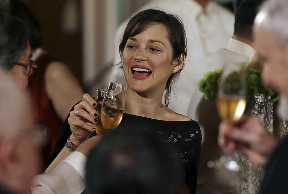 French award-winning actress Marion Cotillard toasts with other guest during a state dinner, at the Malacanang Presidential Palace, in Manila, Philippines, Thursday, Feb. 26, 2015. Cotillard is in the country with French President Francois Hollande on a two-day visit. (AP Photo/Aaron Favila, Pool)