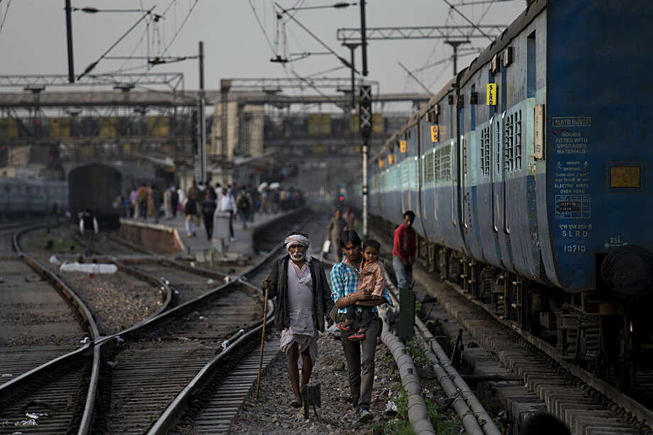 Indian commuters walk between rail tracks in New Delhi, India, Thursday, Feb. 26, 2015. The railways budget unveiled Thursday by Railway Minister Suresh Prabhu envisions $137 billion being invested over the next five years to modernize trains and stations, improve safety and sanitation and expand the reach of the rails in the system that serves more than 23 million passengers a day. (AP Photo/Bernat Armangue)
