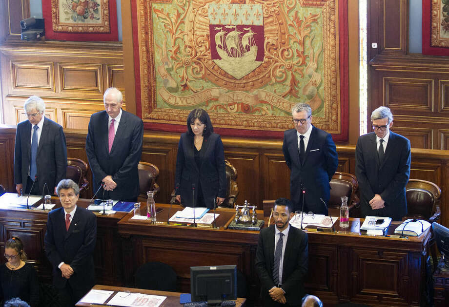 Brussels Mayor Yvan Mayeur, second right, and Paris Mayor Anne Hidalgo, center, observe a minute of silence at the Paris city hall, Tuesday, March 29, 2016. Mayeur is meeting Parisian first responders and holding a minute of silence for victims of last week's attack on Brussels' airport and subway system, and for victims of a weekend attack in Lahore, Pakistan. (AP Photo/Jacques Brinon)