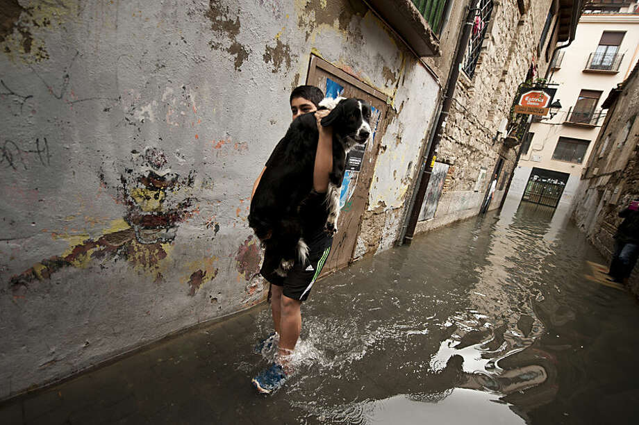 EDS NOTE : SPANISH LAW REQUIRES THAT THE FACES OF MINORS ARE MASKED IN PUBLICATIONS WITHIN SPAIN. A young boy carries his dog as he walks along a flooded street, in Tudela, northern Spain, Friday, Feb. 27, 2015. Heavy rain has lead to widespread flooding in northern Spain over the past few days, especially in Navarra province. (AP Photo/Alvaro Barrientos)