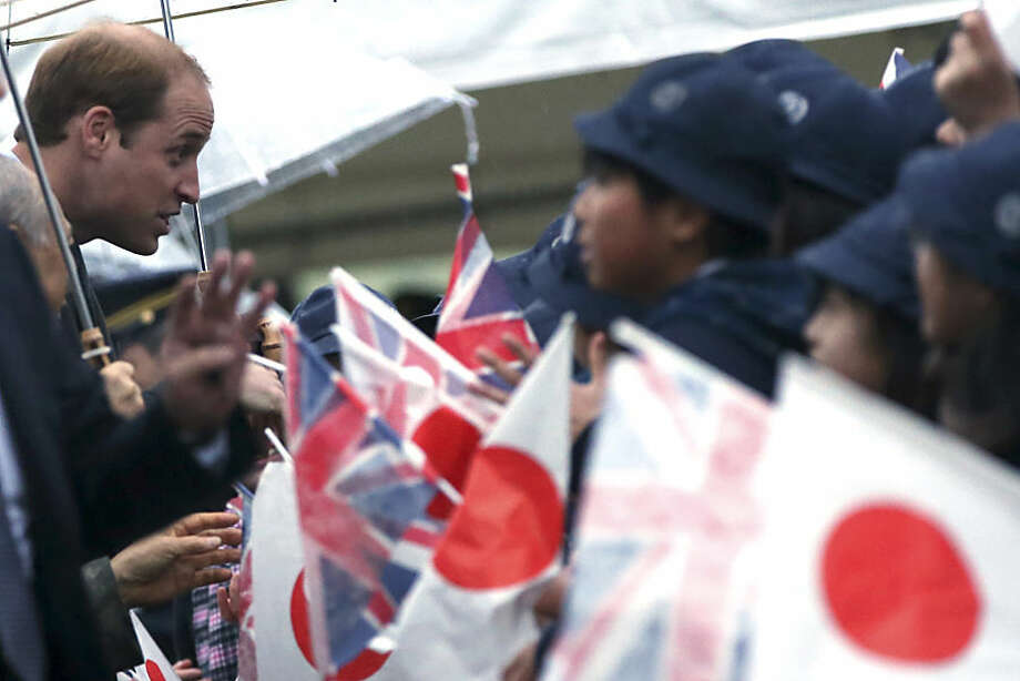 Britain's Prince William, left, greets local students upon arrival at Hamarikyu Gardens in Tokyo Thursday, Feb. 26, 2015. William is having afternoon tea, but it will be green and served by a master in the Japanese ceremonial art in a traditional tea house. (AP Photo/Eugene Hoshiko)