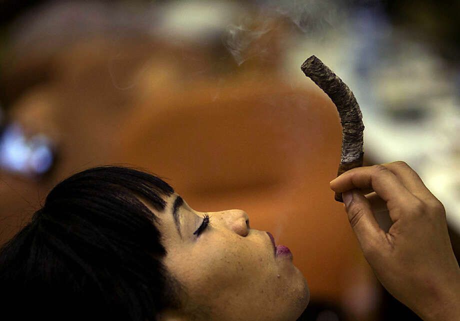 "Daylin Lopez, 30, smokes a cigar during the longest ash competition at the annual Cigar Festival in Havana, Cuba, Thursday, Feb. 26, 2015. As Havana celebrated the annual festival that wraps up with a gala-dinner bash on Friday, officials said that this year alone, they expect to double on-island sales of hand-rolled cigars, known here as ""habanos,"" from 3 million to 6 million. (AP Photo/Ramon Espinosa)"