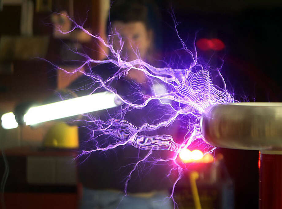 Instructor Robert Callier lights up a bulb with a Tesla coil that he built with students at Haney Technical School, Thursday, Feb. 26, 2015, in Panama City, Fla. (AP Photo/News Herald, Andrew Wardlow)