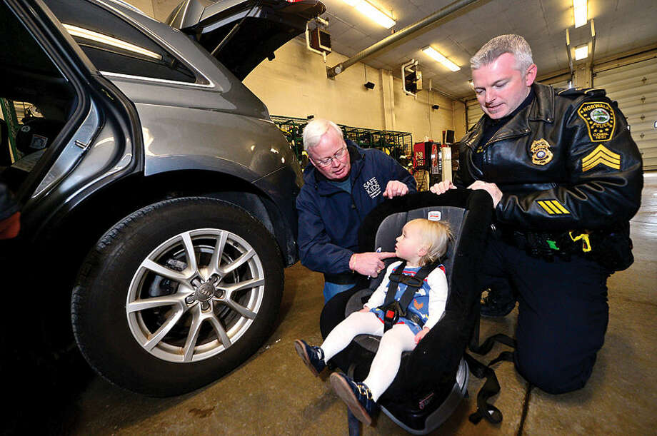 Hour photo / Erik Trautmann Mark Blake of Safe Kids CT and Norwalk Police Sgt Terry Blake assist Clara Denoyre as get properly secured in her seat as The Norwalk Department of Police Services, Fairfield County Safe Kids and The Norwalk Fire Department as they host a free Car Seat Safety Check at Norwalk Fire Station 4 on Westport Ave Friday.