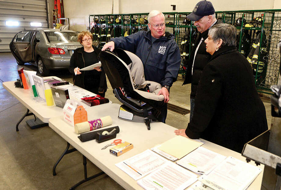 Hour photo / Erik Trautmann Pat Zainc, WATS Grant Coordinator and Mark Blake, Safekids CT Coordinator, assist grandparents Wayne and Hilary Caldwell proper child car seat installation as The Norwalk Department of Police Services, Fairfield County Safe Kids and The Norwalk Fire Department in hosting a free Car Seat Safety Check at fire station 4 on Westport Ave Friday.