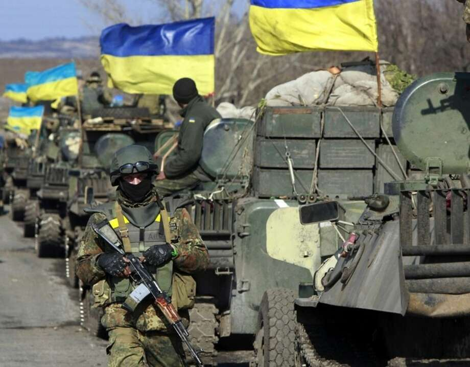 A Ukrainian serviceman stands guard alongside armored vehicles with heavy weapns in tow and flying the Ukrainian on a road in the village of Fedorivka, eastern Ukraine, Friday, Feb. 27, 2015. Ukrainian and Russian-backed separatist forces drew back some heavy weapons from the front line in the east Friday in compliance with a cease-fire deal, although officials in Kiev accused rebels of falling short of requirements. (AP Photo/Sergei Chuzavkov)