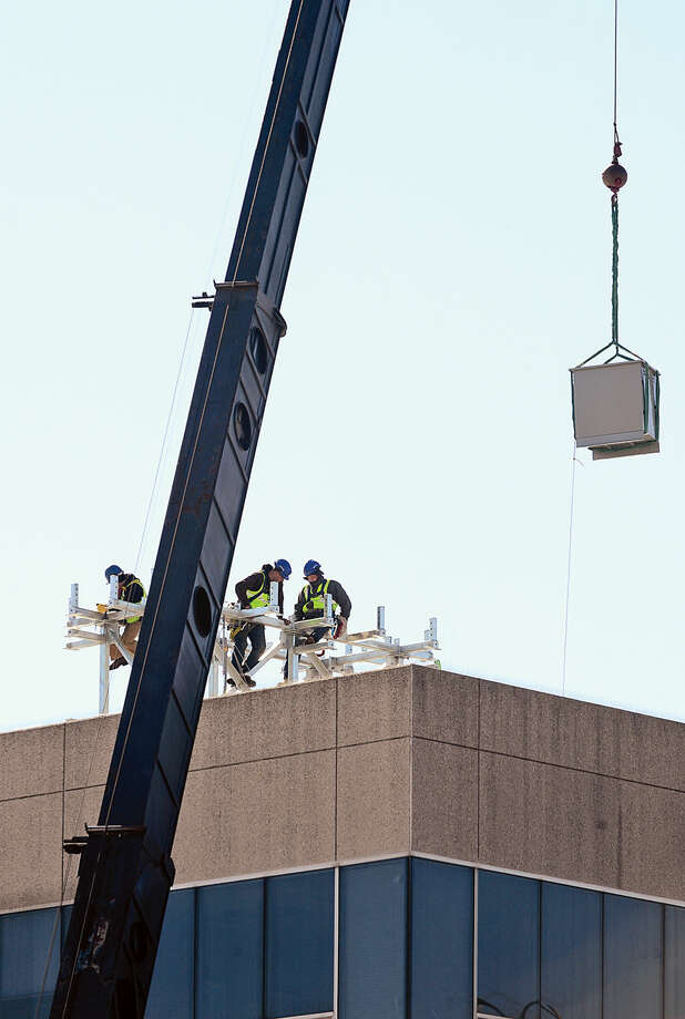 Hour photo / Erik Trautmann Workers install telecommunications equipment on the roof of one Selleck St in Norwalk Friday.