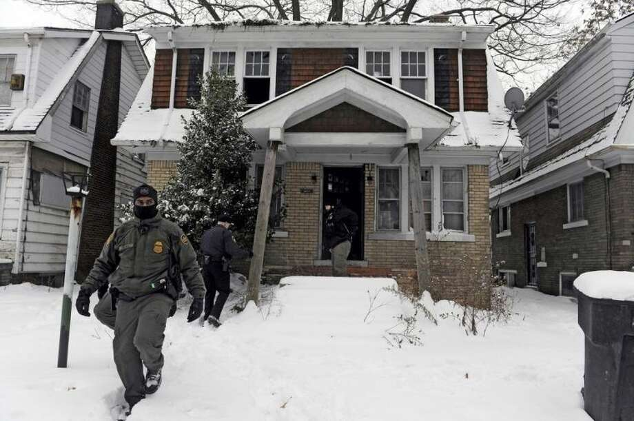"ADVANCE FOR USE SUNDAY, FEB. 23, 2014 AND THEREAFTER - FILE- In this Dec. 17, 2013 file photo, law enforcement officers walk out of a vacant house as several police agencies clear the area during ""Operation Mistletoe,"" a raid targeting drug dealers on Detroit's west side. Many residents have cheered the raids. But even a few of those arrested have actually offered thanks. ""They understand it's time for someone to come in and put an end to this. There's no secret,"" says Elvin Barren, commander of the organized crime division. After a raid one handcuffed suspect, talking with a TV reporter, endorsed the work of Police Chief James Craig and his department: ""Keep up the good work,"" he declared. ""Keep my family safe."" (AP Photo/Detroit News, Steve Perez)"