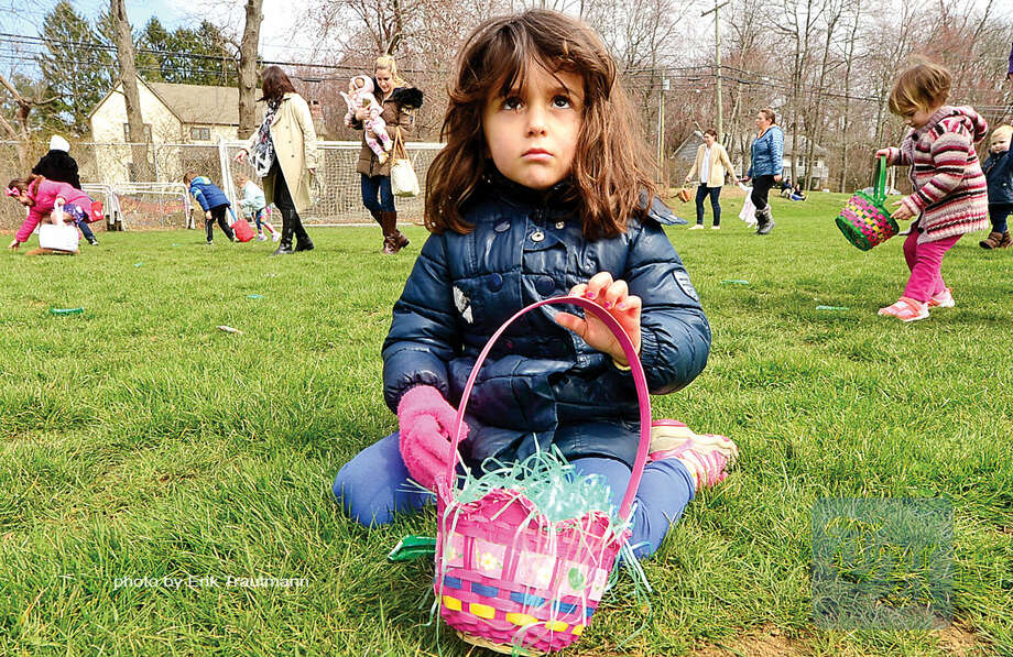Hour photo / Erik Trautmann Eva Astolfi, 3, looks for candy during The Greens Farms Volunteer Fire Company 65th annual Easter Egg Hunt Saturday at Long Lots Elementary School in Westport