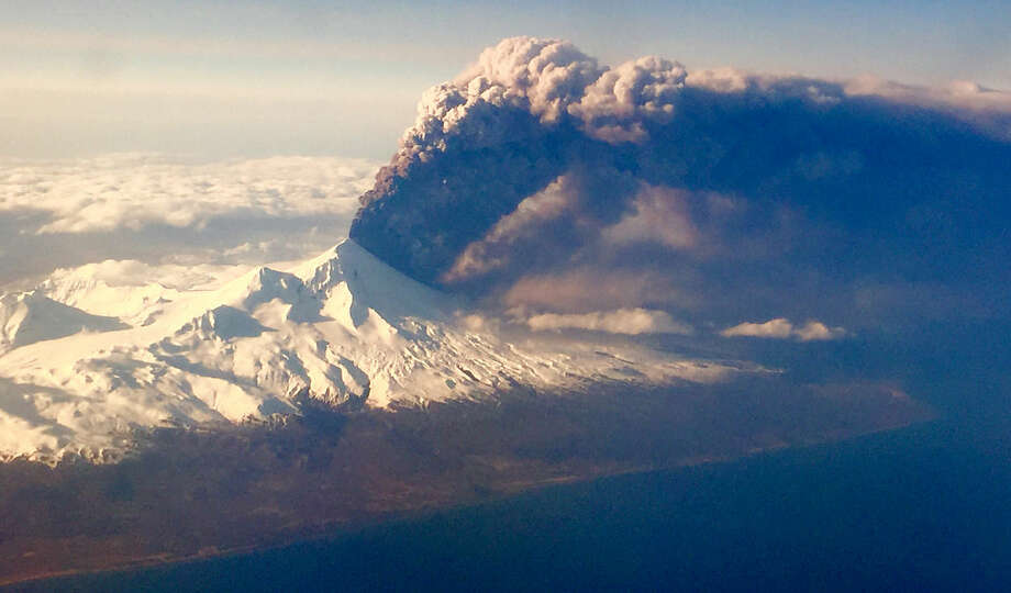 In this Sunday, March 27, 2016, photo, Pavlof Volcano, one of Alaska's most active volcanoes, erupts, sending a plume of volcanic ash into the air. The Alaska Volcano Observatory says activity continued Monday. Pavlof Volcano is 625 miles southwest of Anchorage on the Alaska Peninsula, the finger of land that sticks out from mainland Alaska toward the Aleutian Islands. (Colt Snapp via AP) MANDATORY CREDIT