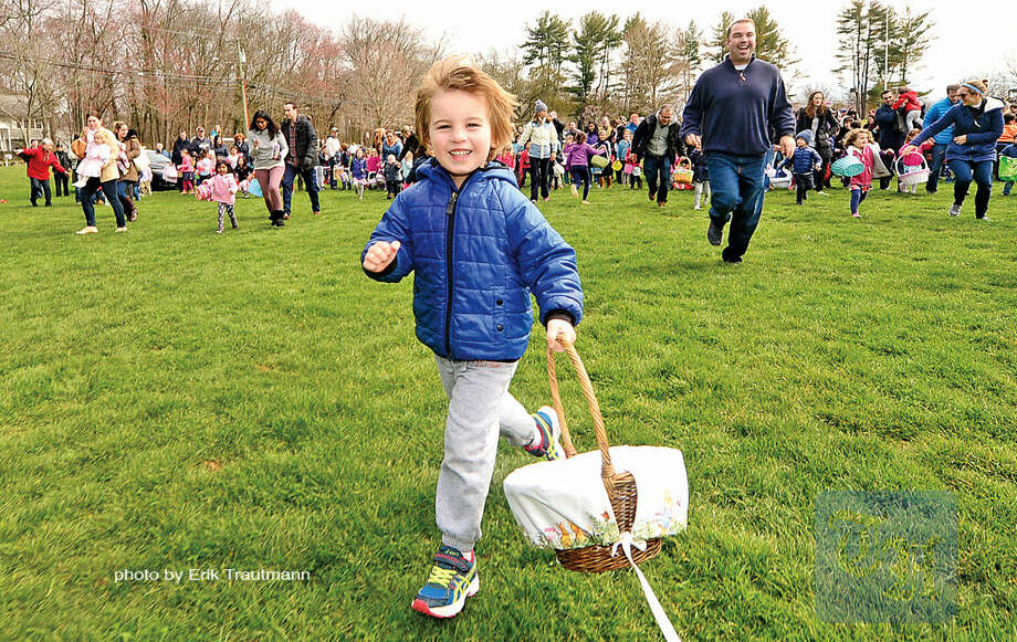 Hour photo / Erik Trautmann 3 year old Brody Michaels heads out to collect candy during The Greens Farms Volunteer Fire Company 65th annual Easter Egg Hunt Saturday at Long Lots Elementary School in Westport