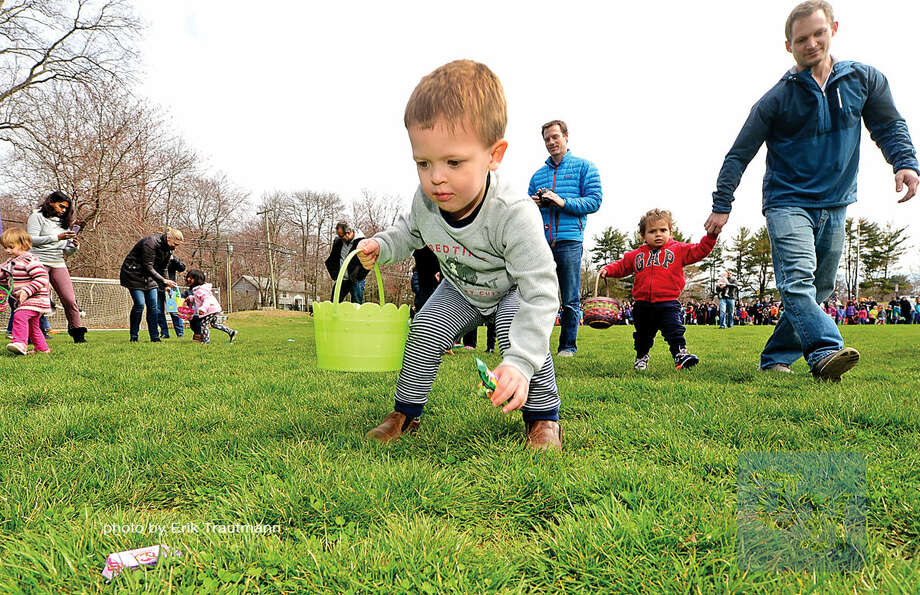 Hour photo / Erik Trautmann 3 year old Jackson Boyd collects candy during The Greens Farms Volunteer Fire Company 65th annual Easter Egg Hunt Saturday at Long Lots Elementary School in Westport