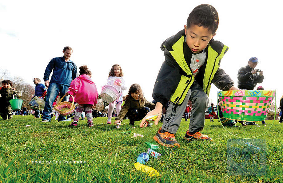 Hour photo / Erik Trautmann Adan Wang, 6, grabs candy during The Greens Farms Volunteer Fire Company 65th annual Easter Egg Hunt Saturday at Long Lots Elementary School in Westport
