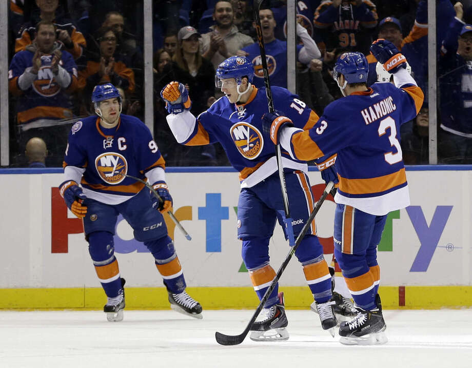 New York Islanders' Ryan Strome, center, reacts after scoring during the first period of the NHL hockey game against the Calgary Flames, Friday, Feb. 27, 2015, in Uniondale, N.Y. (AP Photo/Seth Wenig)