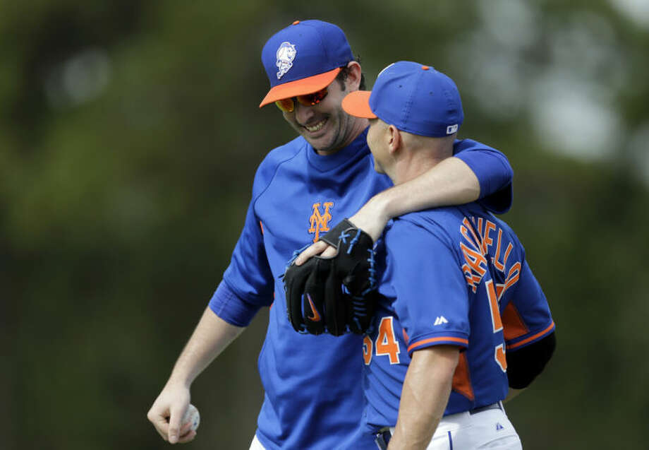 New York Mets pitcher Matt Harvey gets a gives a hug to bullpen catcher Dave Racaniello after the two played catch during spring training baseball practice Saturday, Feb. 22, 2014, in Port St. Lucie, Fla. Harvey underwent Tommy John surgery on Oct. 22. (AP Photo/Jeff Roberson)