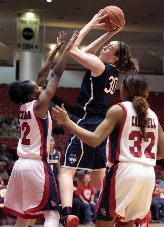 Connecticut forward Breanna Stewart (30) takes a shot over Houston's Destini Texada, left, and Te'Onna Campbell (32) during the first half of an NCCA women's basketball game, Saturday, Feb. 22, 2014, in Houston. (AP Photo/Patric Schneider)