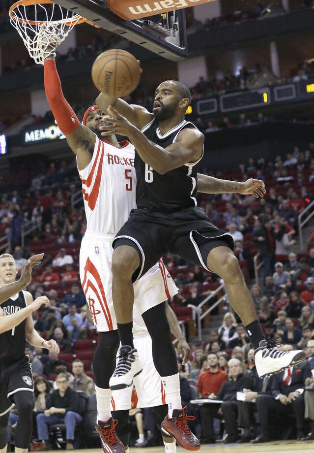 Brooklyn Nets' Alan Anderson (6) passes off the ball under pressure from Houston Rockets' Josh Smith (5) during the first half of an NBA basketball game Friday, Feb. 27, 2015, in Houston. (AP Photo/Pat Sullivan)