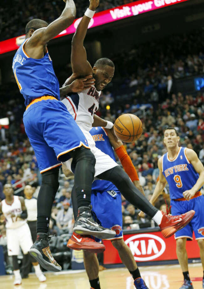 Atlanta Hawks forward Elton Brand (42) is fouled as he goes to the basket against New York Knicks forward Amar'e Stoudemire (1) in the first half of an NBA basketball game Saturday, Feb. 22, 2014, in Atlanta. (AP Photo/John Bazemore)