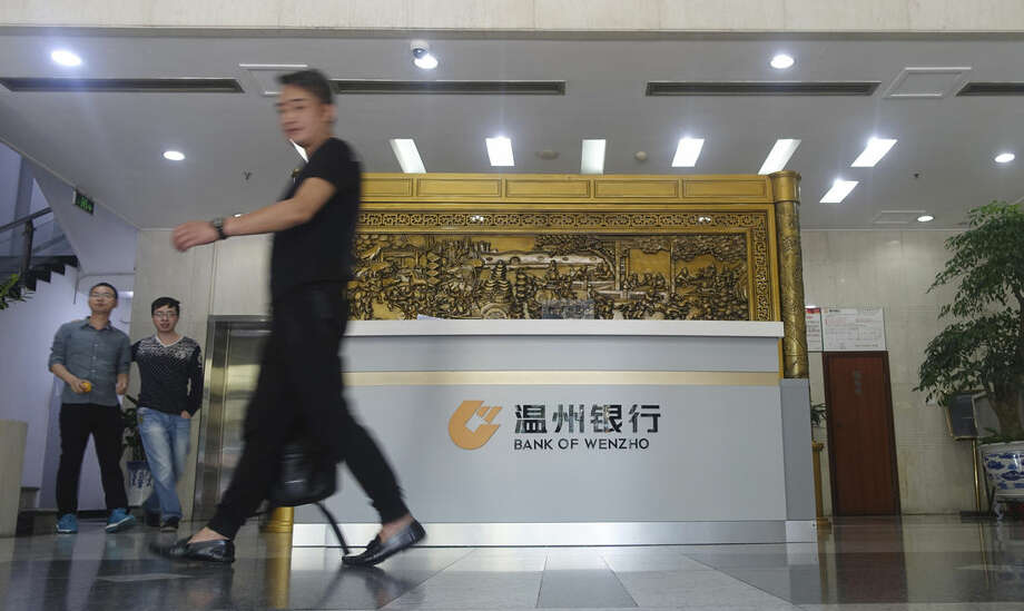 In this photo taken Wednesday, Oct. 21, 2015, a man walks through the lobby of the Bank of Wenzhou headquarters in Wenzhou, China. Sophisticated cyber-thieves tricked Mattel Inc. into sending over $3 million to an account at the Bank of Wenzhou, which is headquartered in Wenzhou city, a gritty enclave on China's eastern coast that is emerging as a significant transit point in global money laundering networks. (AP Photo/Erika Kinetz)