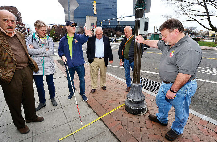 Hour photo / Erik Trautmann Stamford's Access For All Committee members including Phil Magalnick, center, point out sidewalk obstructions as the committee performs a walkthrough of Downtown Stamford as part of the City's efforts to outline ADA compliance for outdoor dining establishments.