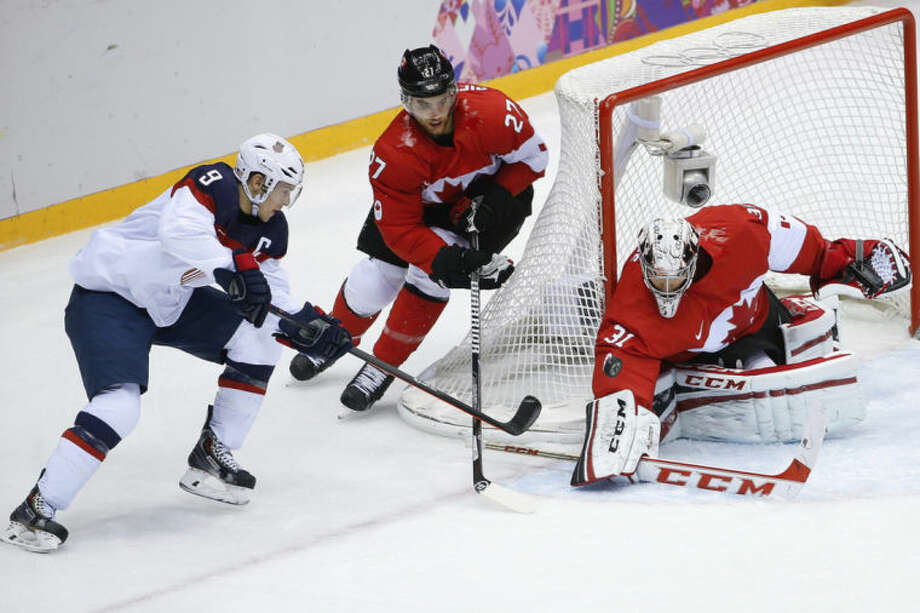 Canada goaltender Carey Price blocks a shot at the goal by USA forward Zach Parise as Canada defenseman Alex Pietrangelo skates into help protect the goal during the men's semifinal ice hockey game at the 2014 Winter Olympics, Friday, Feb. 21, 2014, in Sochi, Russia. (AP Photo/Matt Slocum)