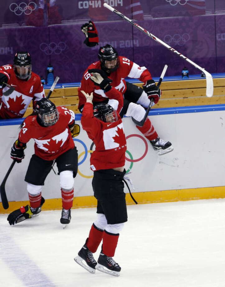 The Canada bench erupts after Marie-Philip Poulin of Canada (29) scores the game-winning goal in overtime against the USA during women's gold medal ice hockey game at the 2014 Winter Olympics, Thursday, Feb. 20, 2014, in Sochi, Russia. (AP Photo/Petr David Josek)