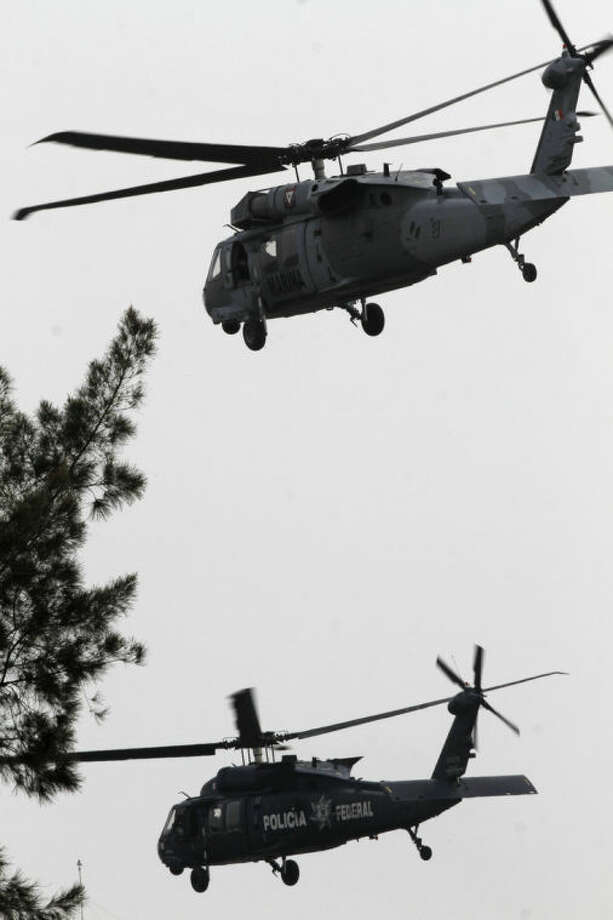 "A Mexican navy helicopter, top, escorts a federal police helicopter transporting Joaquin ""El Chapo"" Guzman, after taking off from the Navy hanger in Mexico City, Mexico, Saturday, Feb. 22, 2014. The world's most-wanted drug lord, Guzman, arrived at the Mexico City airport after his arrest early Saturday and was being taken directly to prison, said Attorney General Jesus Murillo Karam. (AP Photo/Marco Ugarte)"