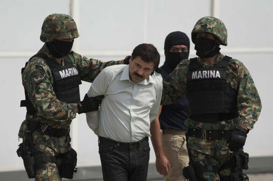 "Joaquin ""El Chapo"" Guzman is escorted to a helicopter in handcuffs by Mexican navy marines at a navy hanger in Mexico City, Mexico, Saturday, Feb. 22, 2014. A senior U.S. law enforcement official said Saturday, that Guzman, the head of Mexicoís Sinaloa Cartel, was captured alive overnight in the beach resort town of Mazatlan. Guzman faces multiple federal drug trafficking indictments in the U.S. and is on the Drug Enforcement Administrationís most-wanted list. (AP Photo/Eduardo Verdugo)"