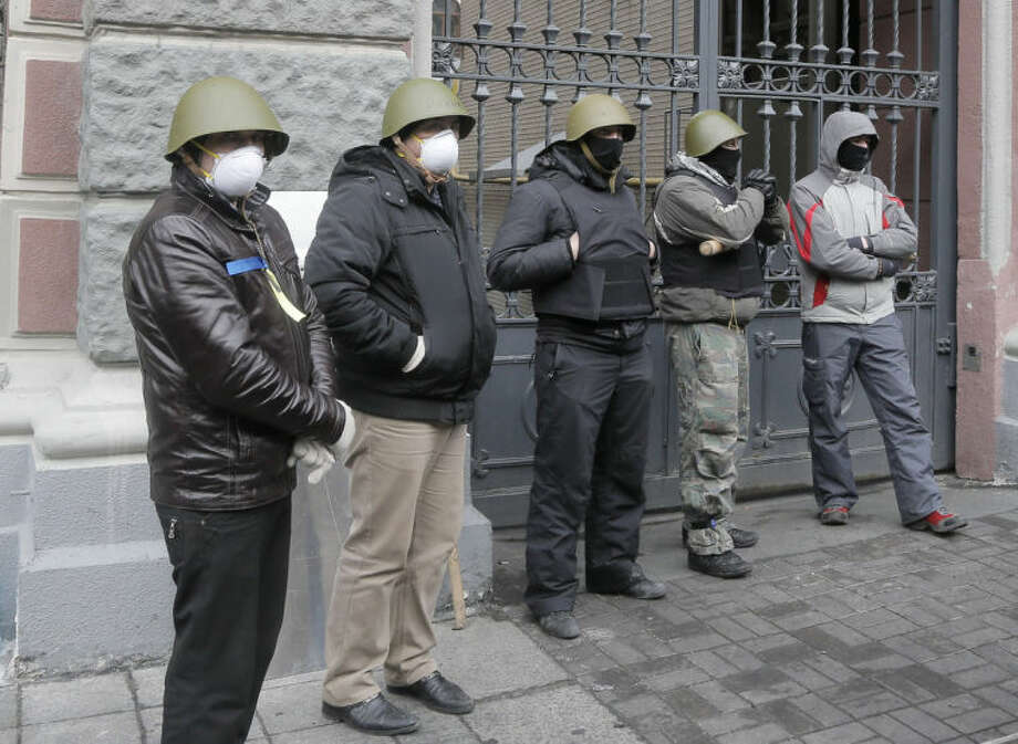 Activists guard Ukraine's National Bank close to Kiev's Independence Square, the epicenter of the country's recent unrest, Ukraine, Sunday, Feb. 23, 2014. Volunteers from among Independence Square protesters protect the government buildings from vandalism and marauding. (AP Photo/Efrem Lukatsky)