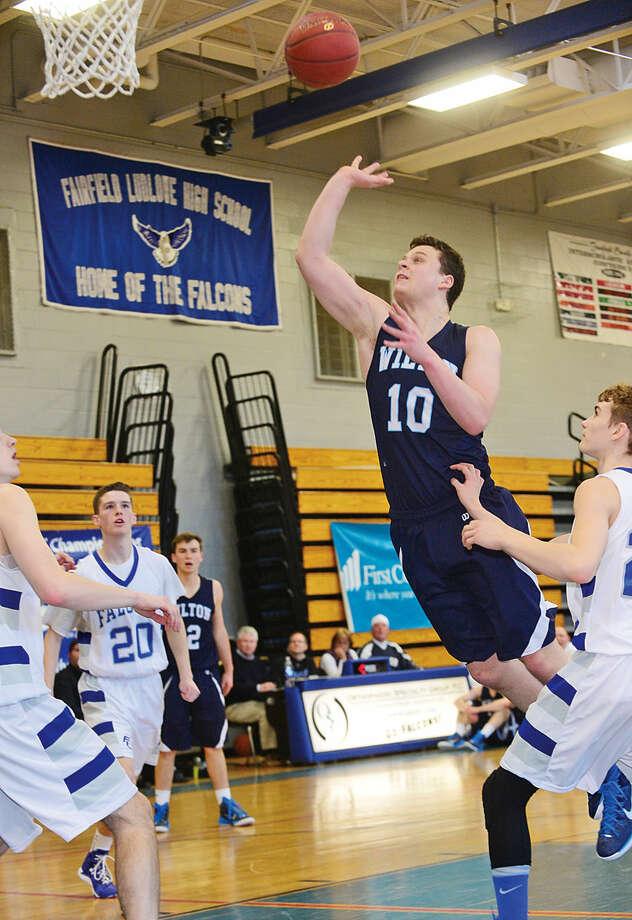 Hour photo / Erik Trautmann Wilton takes on Fairfield Ludlowe in the FCIAC boys basketball quarterfinals at Ludlowe High School Saturday