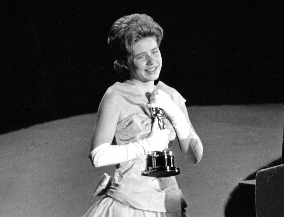 """FILE - In this April 8, 1963 file photo, actress Patty Duke, 16, accepts the Oscar as best supporting actress for her work in """"The Miracle Worker"""" at the annual Academy Awards in Santa Monica, Calif. Duke, who won an Oscar as a child at the start of an acting career that continued through her adulthood, died Tuesday, March 29, 2016, of sepsis from a ruptured intestine. She was 69. (AP Photo, File)"""