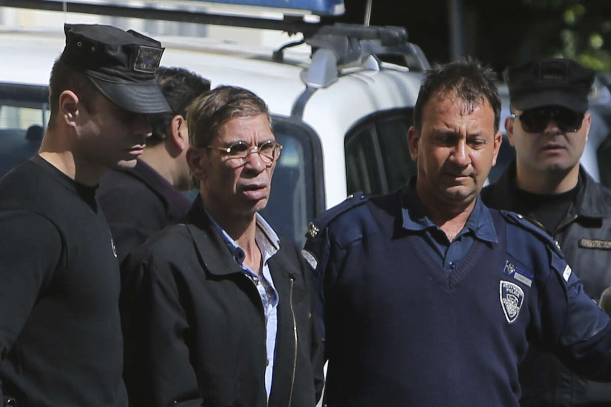 EgyptAir plane hijacking suspect Seif Eddin Mustafa, second left, is escorted by Cyprus police officers as he leaves a court after a remand hearing as authorities investigate him on charges including hijacking, illegal possession of explosives and abduction in the Cypriot coastal town of Larnaca Wednesday, March 30, 2016. Mustafa described as