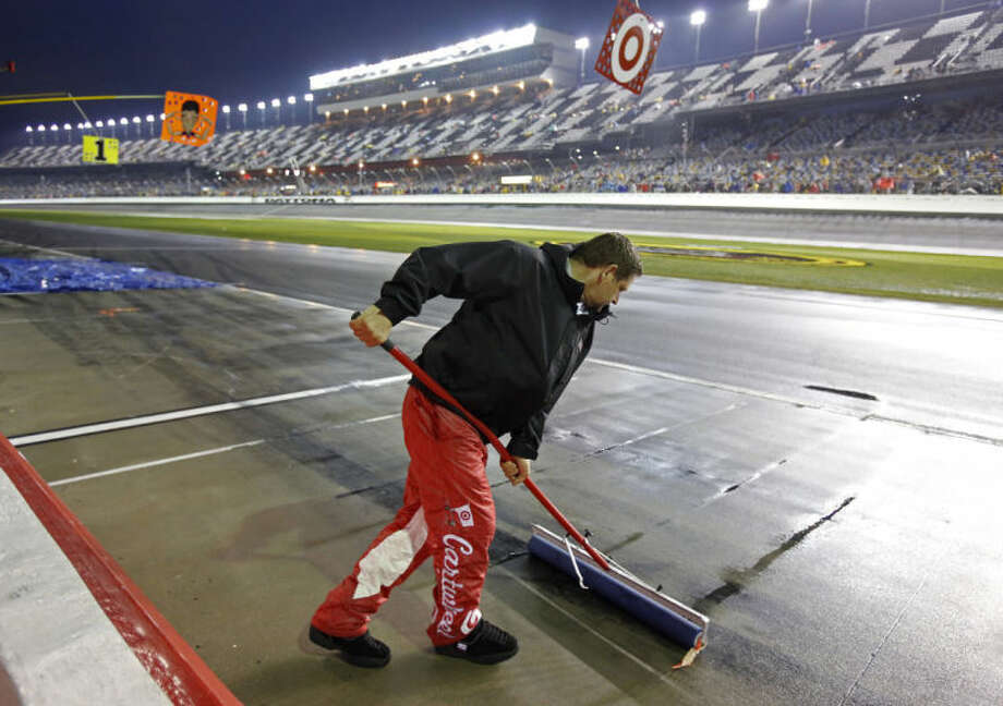 A crew member uses a squeegee to remove water from pit road during a rain delay in the NASCAR Daytona 500 Sprint Cup series auto race at Daytona International Speedway in Daytona Beach, Fla., Sunday, Feb. 23, 2014. (AP Photo/Terry Renna)